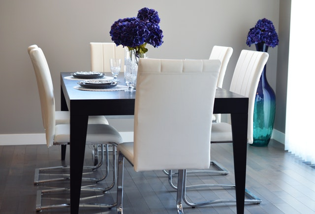 A Vibrant Shade Of Blue Flowers On The Black Table Will Boost Color Scheme Your Dining Room Clean Walls And White Chairs In Contrast With